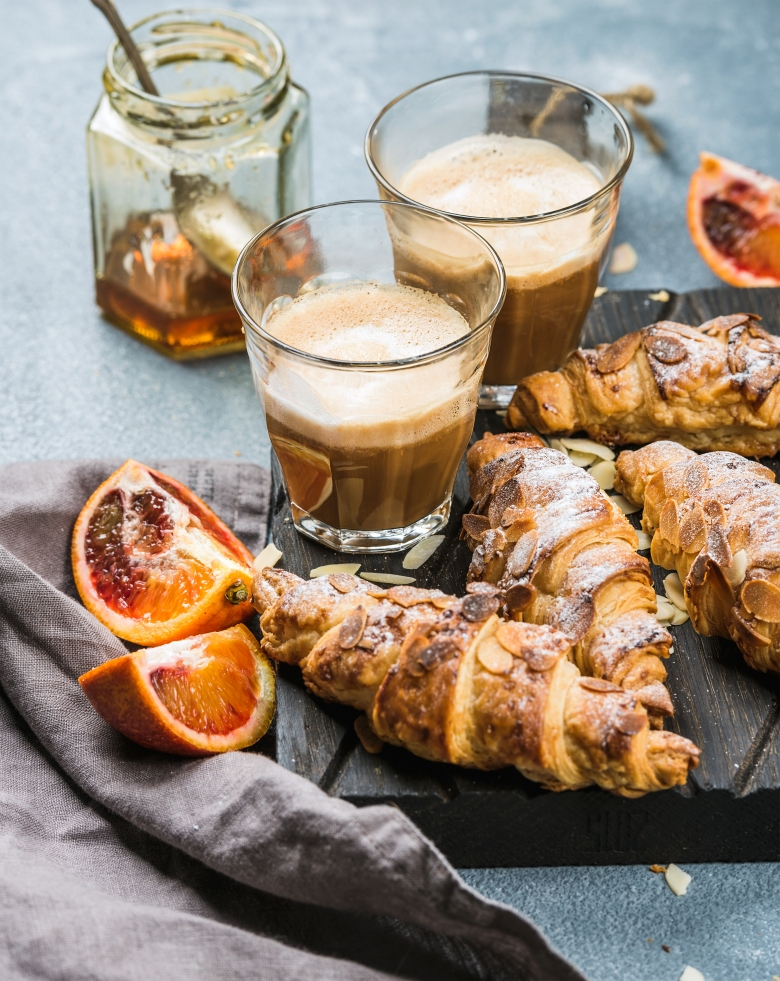 Traditional Italian style home breakfast. Latte in glasses, almond croissants and red bloody Sicilian oranges over concrete textured table